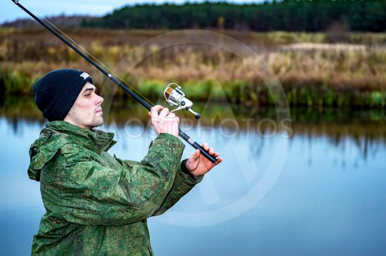 Male angler catches on a spinning fish in cold water in...