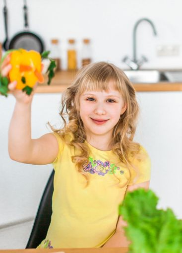 Cute  little girl play with salad at kitchen
