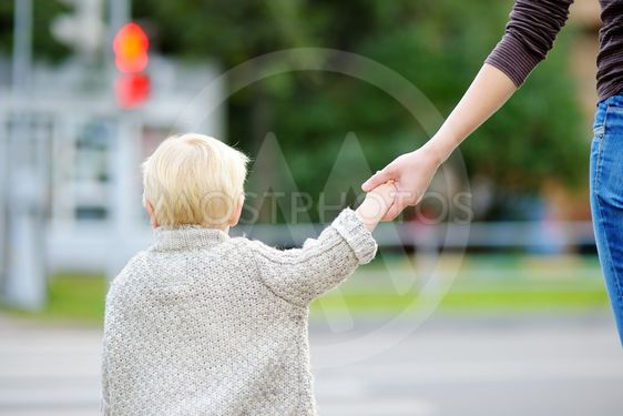 Mother and toddler crossing the street on the crosswalk