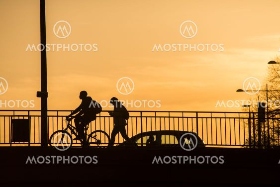 Silhouette of people walking and riding a bike by sunset