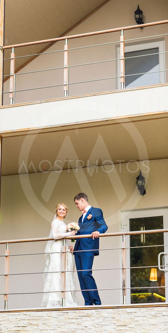 the bride and groom on a balcony