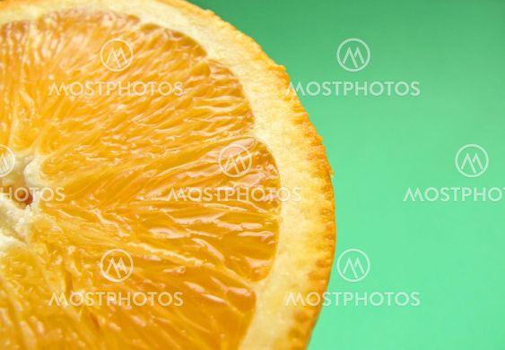 sliced orange macro on green background