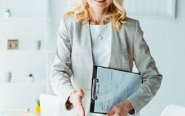attractive blonde woman in glasses holding clipboard and...