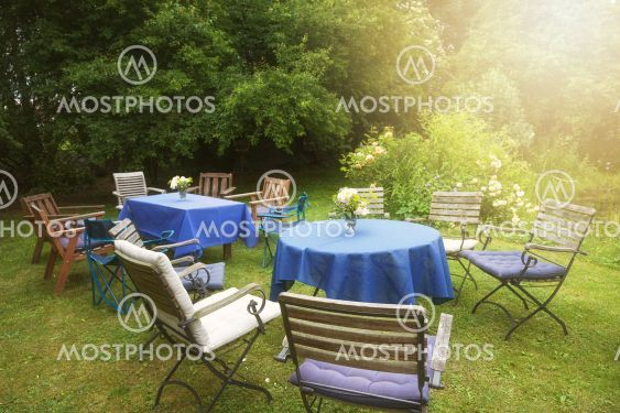 Set up for a private garden party with tables, blue...