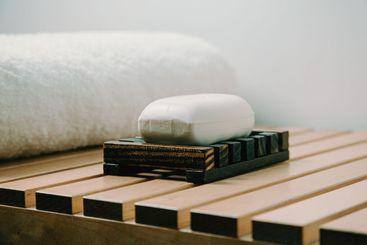 A hard soap over a wooden soap dish in a bathroom with a...