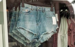 torn up jeans short on hangers in a fashion...