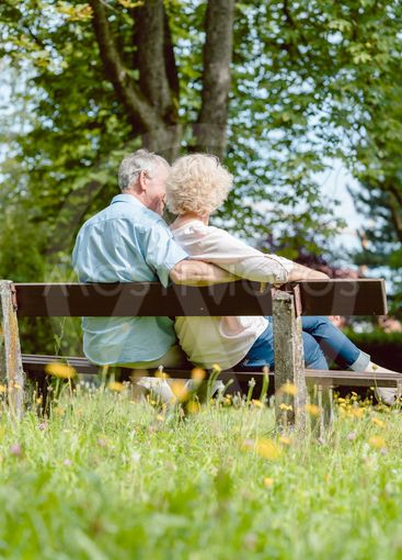 Romantic elderly couple sitting together on a bench in a...
