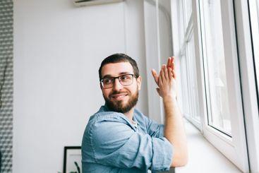 Portrait of smiling caucasian man standing near window...