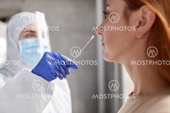 doctor in protective wear making coronavirus test