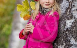 Cute girl playing with autumn leaves in park