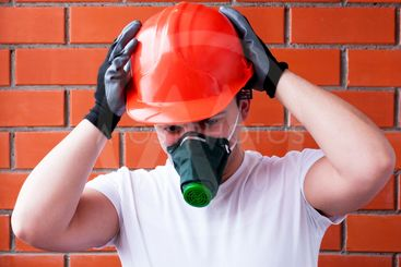 A man in a helmet and respirator performs painting work...