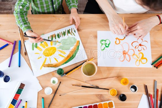 Hands of mother and son painting bright colorful pictures