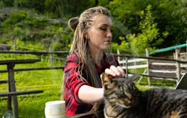 Young lady scratching head of feline companion