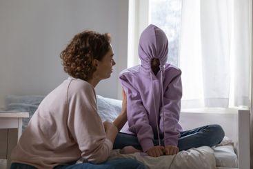 Stubborn teenage girl putting hood on avoiding talk with...