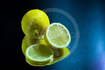 Lemon and slices with reflection on mirror