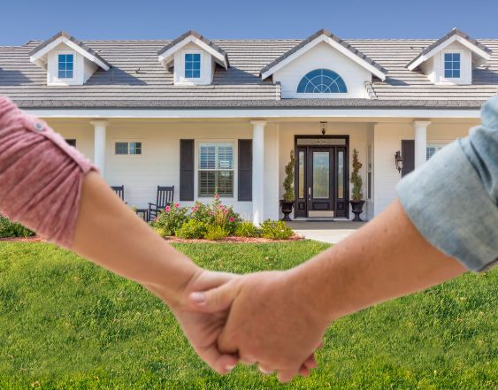 Couple Holding Hands Approaching Front Door Of New House