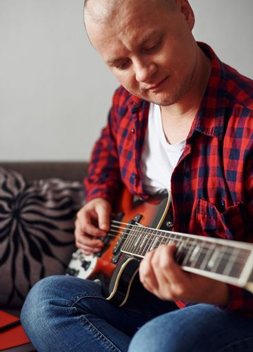Stylish guy learning to play the guitar at home. Video...
