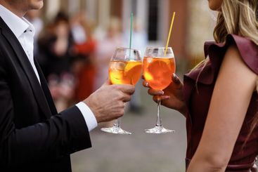 young couple drinking a cocktail.hands of two people...