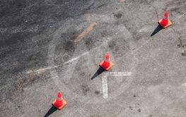 Three red warning road cones stand in line