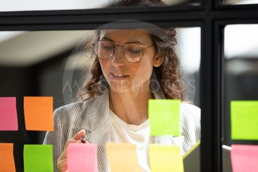 Young businesswoman write ideas on sticky notes on glass...