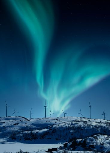 Wind power plants on a hill in winter night with...