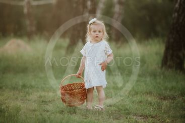 Beautiful baby girl walking in a sunny garden with a...