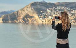 Rear view woman holding smartphone take photography of...