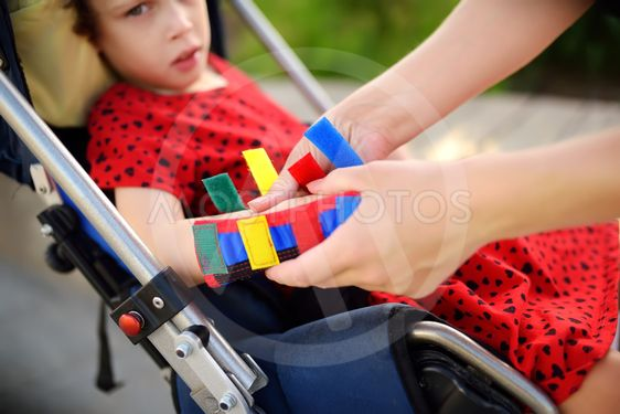 Mother puts orthosis on her daughter arms. Disabled girl...