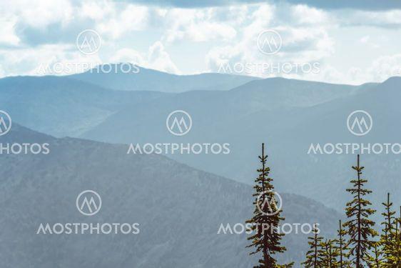 Scenic view of misty mountain valley. Gentle hills under...