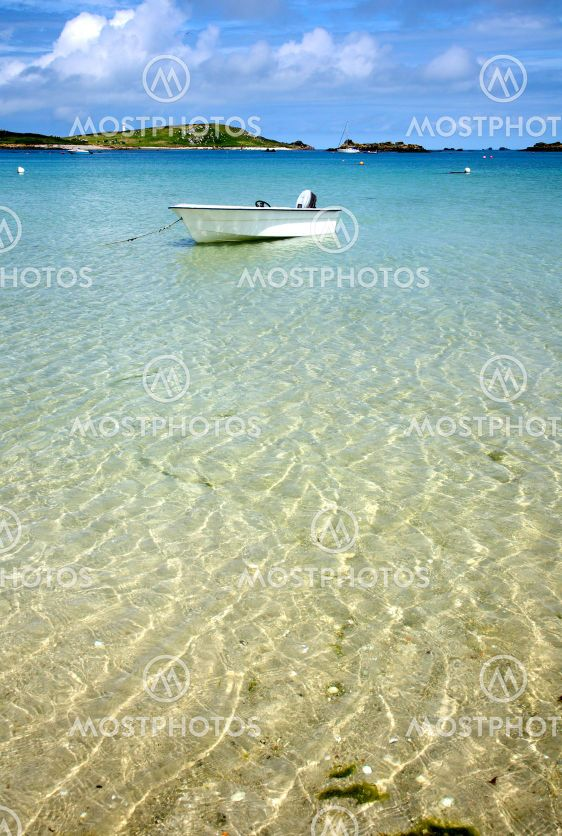 A white boat floating on clear sea, Isles of Scilly,...
