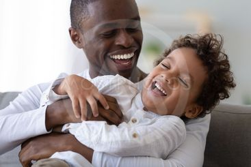 Happy black father tickling african kid son laughing...
