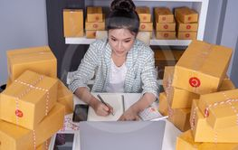 young woman entrepreneur checking and writting order with...