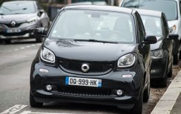 Front view of black smart car parked in the street