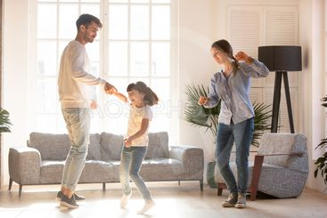 Family dancing in living room spending time on weekend...