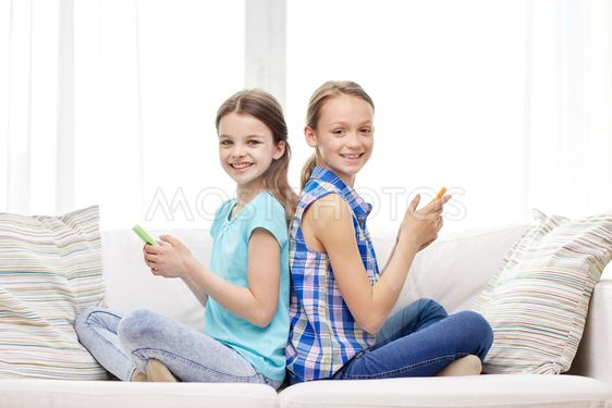 happy girls with smartphones sitting on sofa