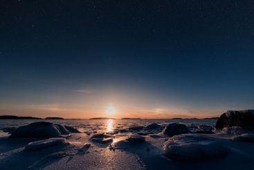Epic winter landscape with setting sun and stars