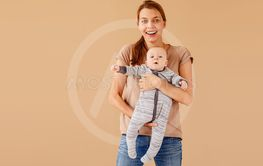 Exited woman with baby in hands looking at camera