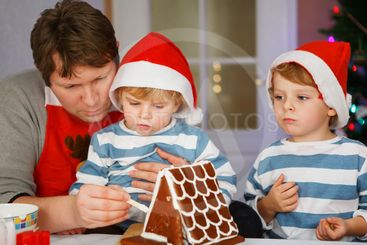 Father and two little sons preparing a gingerbread cookie...