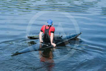 The athlete floats on the river in a kayak with the flow...