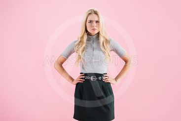beautiful angry woman looking at camera, isolated on pink