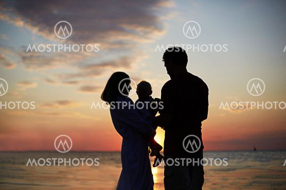 The silhouette of the family mom, dad child against the...