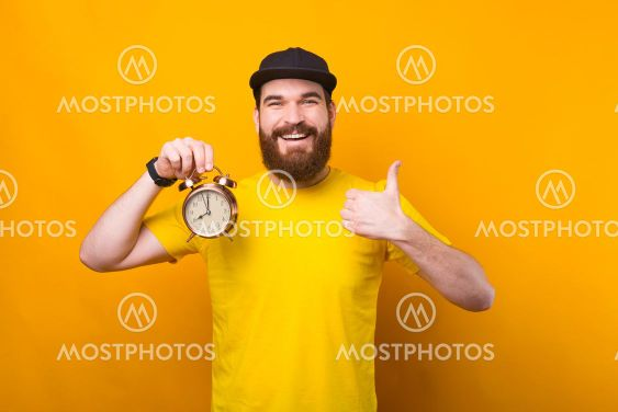 Photo of young hipster man holding alarm clock and...
