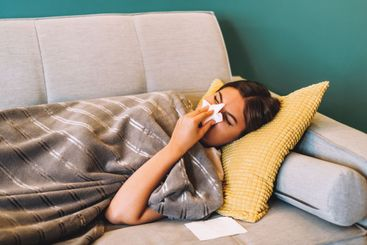 Sick young woman blowing her nose using facial tissues...
