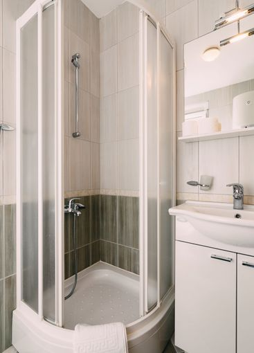 Open empty shower stall and washbasin in the bathroom...