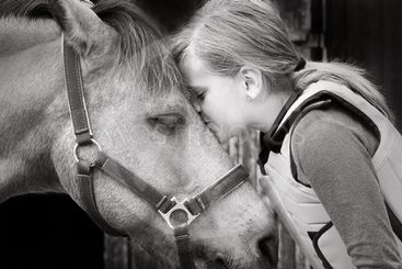 Giirl  kissing her horse