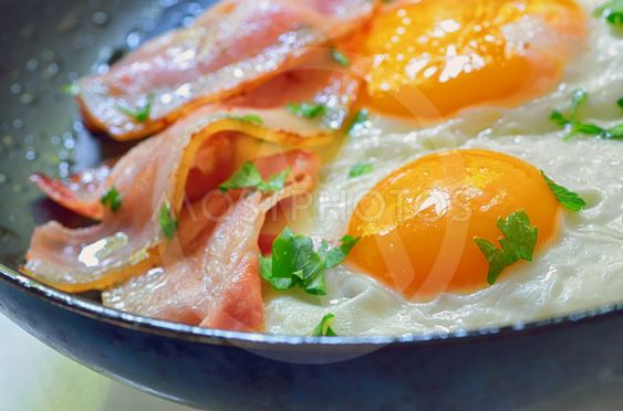 fried egg with bacon in a frying pan