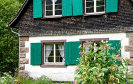quaint country cottage with green shutters