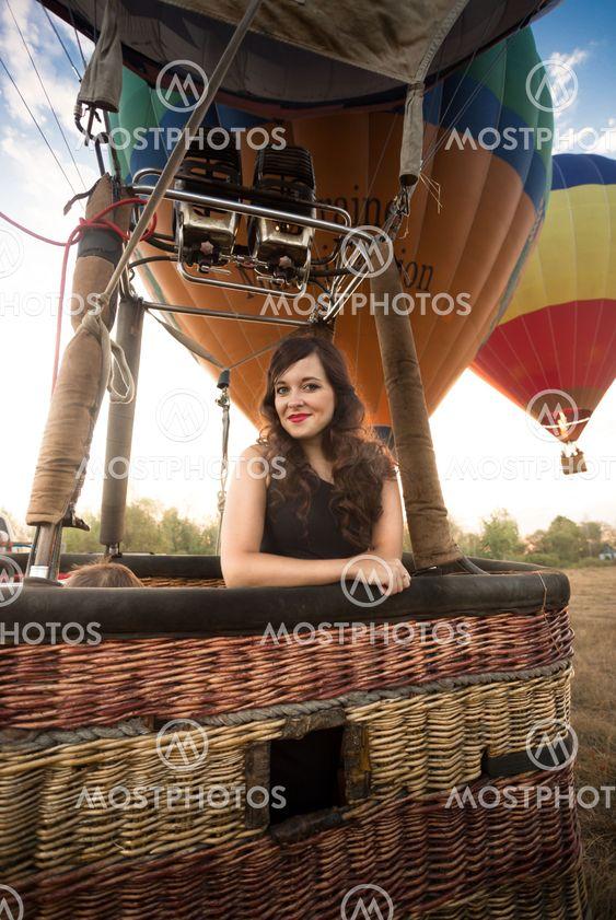 Portrait of beautiful woman posing at hot air balloon...