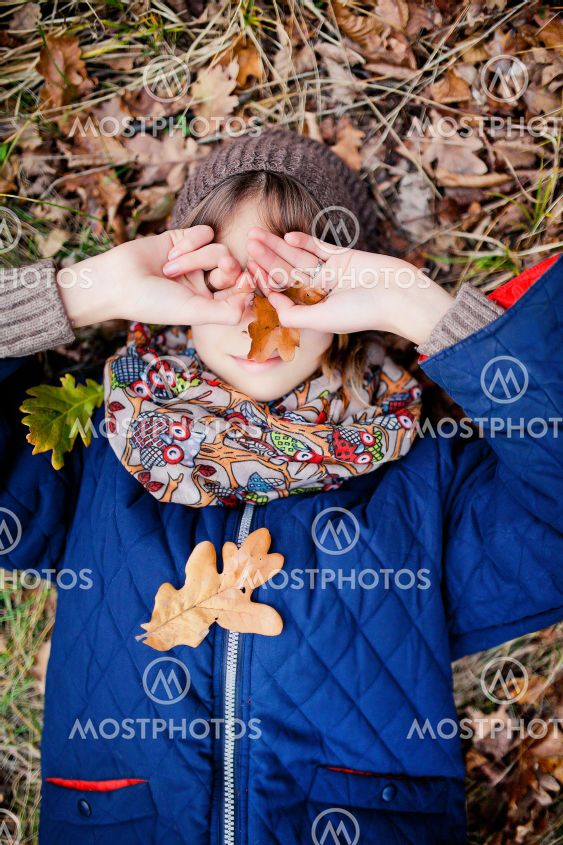 Girl lies on autumn leaves and covers her face