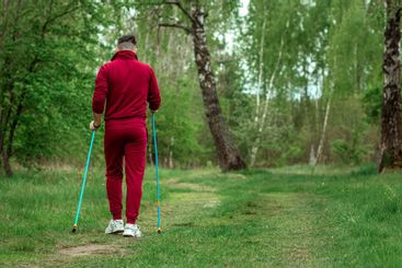 A man in a tracksuit is engaged in Nordic walking. The...